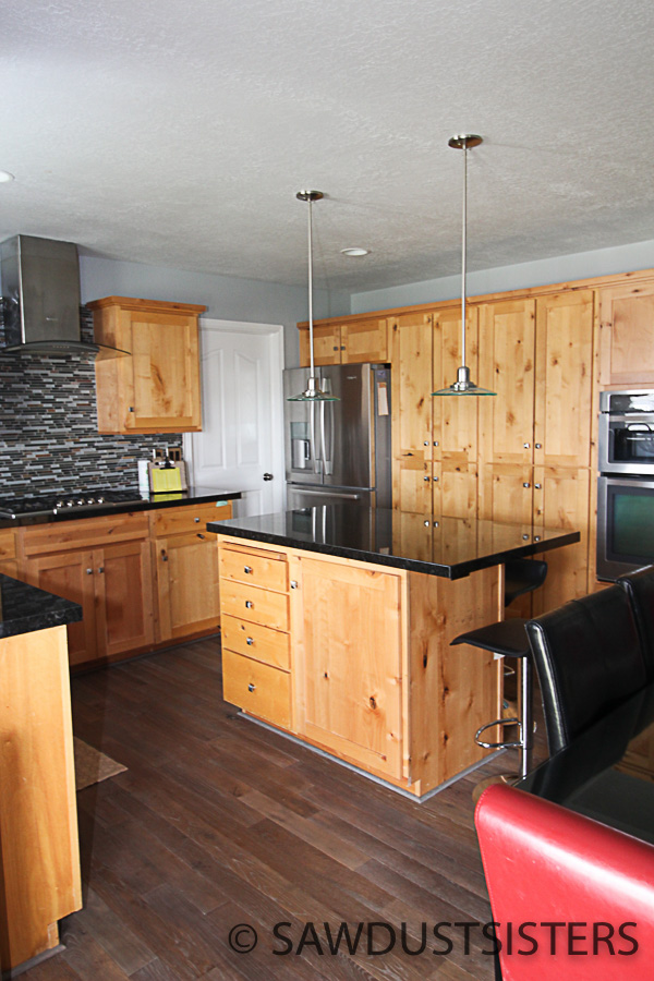 CLICK TO SEE THE STUNNING TRANSFORMATION! Migrating from knotty alder to grey kitchen cabinets is a budget-friendly way to give an outdated kitchen a modern look. Whether you do it yourself or hire it out, it is a job that requires a bit of research, motivation, and attention to detail. It took me three years to pull the trigger on this 90's -very- knotty kitchen. But now that it's done, I am thrilled with the results and glad I took the time to think it through.