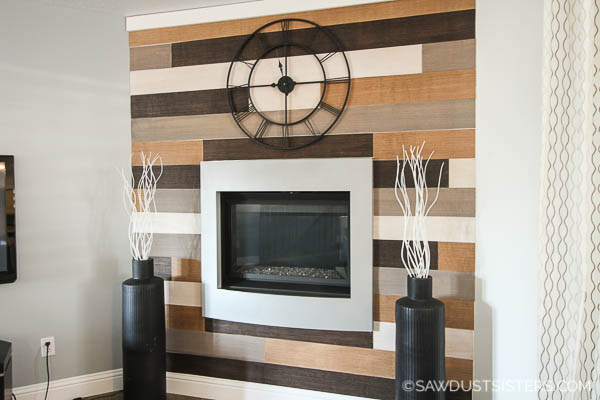 A fireplace plywood surround is an inexpensive way to give a modern fireplace a touch of character. These planks are made from ripped plywood and stained in a variety of colors. You will be amazed at how easy it is to create this look!