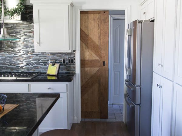 "This beginner- friendly tutorial is a for two sided barn door with rustic decorative trim on both sides. Use wood boards from the big box store and birch plywood for a budget friendly project. This project lays out the steps to build a door of any size while still keeping the 1- 3/4"" door width required by standard sliding barn door hardware. #sawdustsisters #barndoor #slidingbarndoor #doublesidedbarndoor"