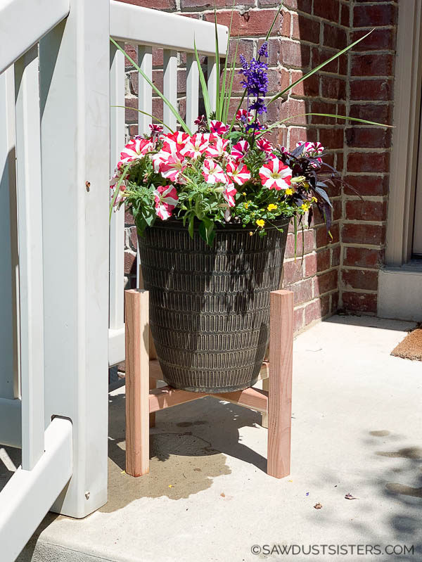 This DIY redwood plant stand is a quick beginner building project that will give your porch some mid century modern flare. The minimalist look adds height to your plants without robbing them space needed to bloom. Adjust the middle piece to fit any size pot. Build singly or in pairs and place on either side of your front door. You can use it indoors or out. What do you think? Are your wheels turning? #sawdustsisters #modernplantstand #midcenturyplantstand #scrapwoodplanter