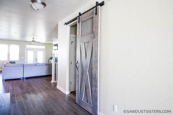 This post will take you a step by step process to build your own barn door with minimal tools. CLICK NOW for the tutorial along with downloadable FREE PLANS. You can apply the simple process to build one to fit your space.